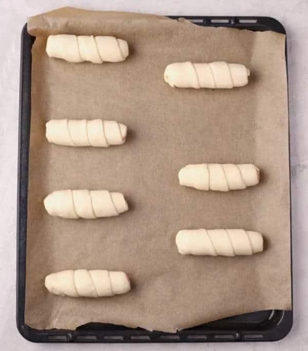 выкладываем завёрнутые в тесто сосиски на противень