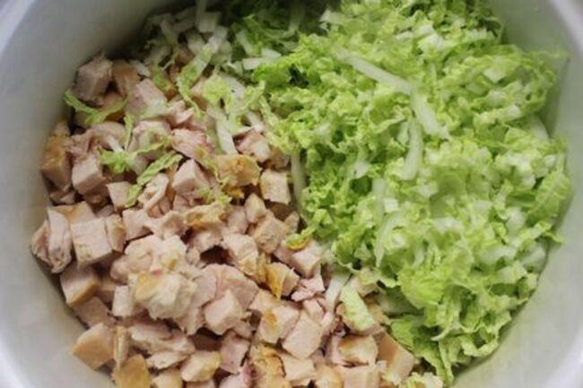 в глубокую емкость выкладываем курицу и капусту