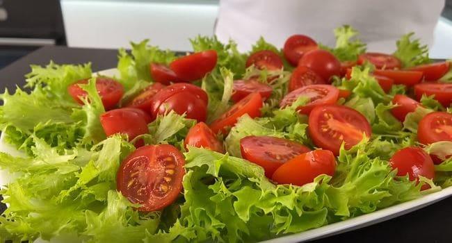на листья салата выкладываю половинки помидорок