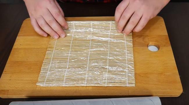 обмотайте циновку пищевой пленкой в два слоя