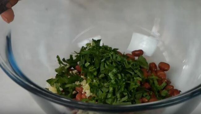 отправляем нарубленный чеснок и нарезанную зелень к фасоли