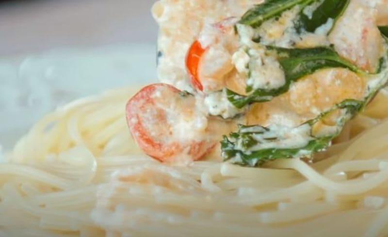 смешиваем спагетти с соусом и креветками в тарелке