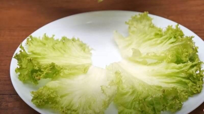 на блюдо выкладываем по кругу листья салата