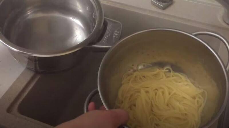 сливаем воду со спагетти при помощи дуршлага